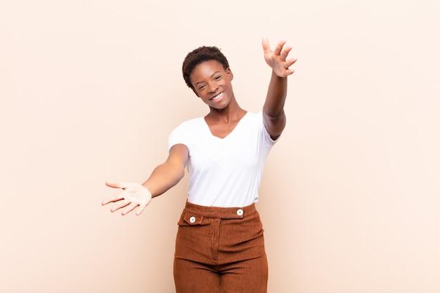 Jonge mooie vrouw die vrolijk glimlacht die een warme, vriendschappelijke, houdende van welkome omhelzing geeft, gelukkig en aanbiddelijk voelt