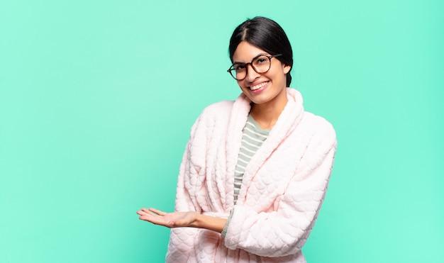 Jonge mooie vrouw die vrolijk glimlacht, zich gelukkig voelt en een concept in exemplaarruimte met handpalm toont. pyjama's concept