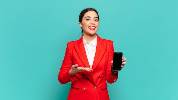 Jonge mooie vrouw die vrolijk glimlacht, zich gelukkig voelt en een concept in exemplaarruimte met handpalm toont