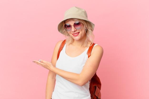 Jonge mooie vrouw die vrolijk glimlacht, zich gelukkig voelt en een concept toont. zomer toeristische concept