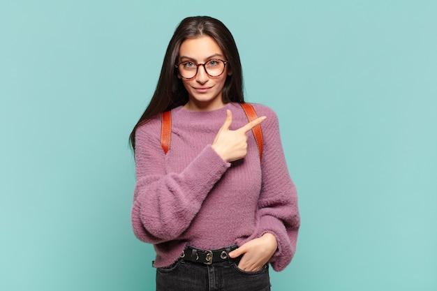 Jonge mooie vrouw die vrolijk glimlacht, zich gelukkig voelt en naar opzij en omhoog wijst, voorwerp in exemplaarruimte toont. student concept