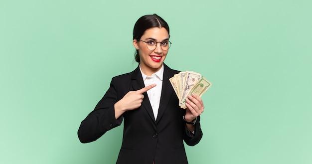Jonge mooie vrouw die vrolijk glimlacht, zich gelukkig voelt en naar opzij en omhoog wijst, voorwerp in exemplaarruimte toont. zaken en bankbiljetten concept