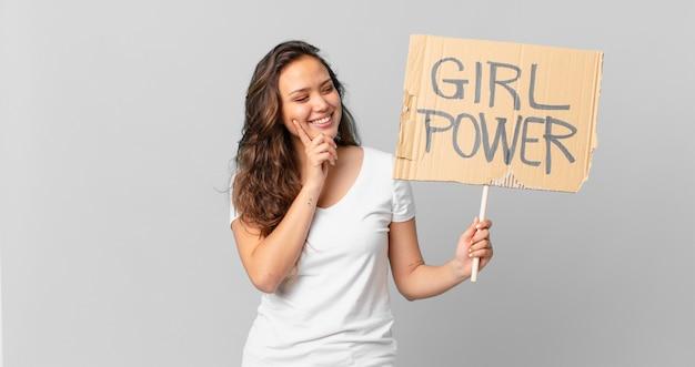 Jonge mooie vrouw die vrolijk lacht en dagdroomt of twijfelt en een girlpower-banner vasthoudt