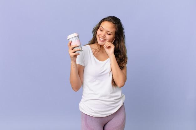 Jonge mooie vrouw die vrolijk lacht en dagdroomt of twijfelt en een kopje koffie vasthoudt