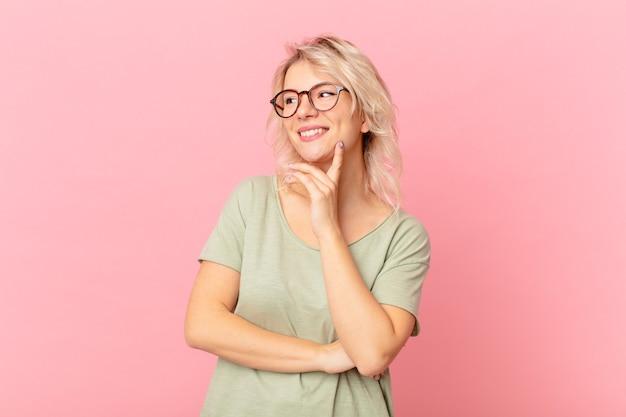 Jonge mooie vrouw die vrolijk lacht en dagdroomt of twijfelt