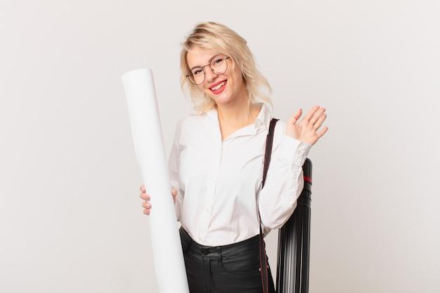 Jonge mooie vrouw die vrolijk lacht, met de hand zwaait, je verwelkomt en begroet. architect concept