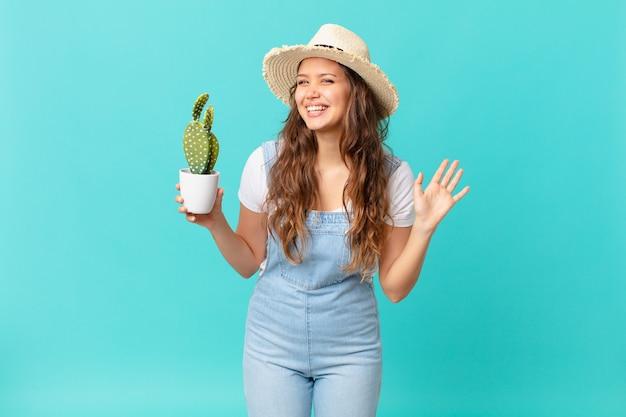 Jonge mooie vrouw die vrolijk lacht, met de hand zwaait, je verwelkomt en begroet en een cactus vasthoudt