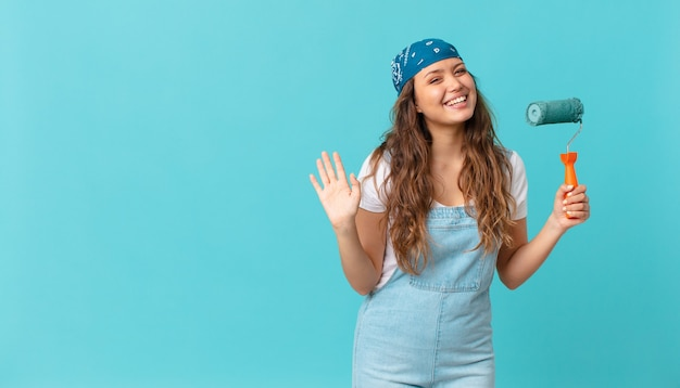 Jonge mooie vrouw die vrolijk lacht, met de hand zwaait, je verwelkomt en begroet en een muur schildert