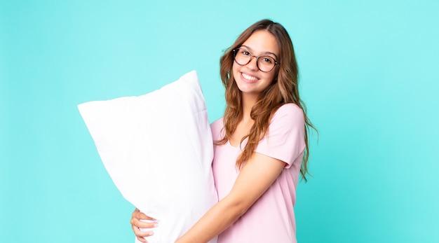 Jonge mooie vrouw die vrolijk lacht met een hand op de heup en zelfverzekerd een pyjama draagt en een kussen vasthoudt