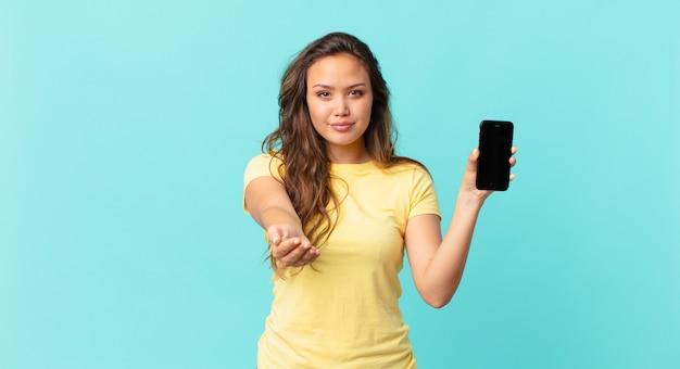 Jonge mooie vrouw die vrolijk lacht met vriendelijk en een concept aanbiedt en toont en een smartphone vasthoudt