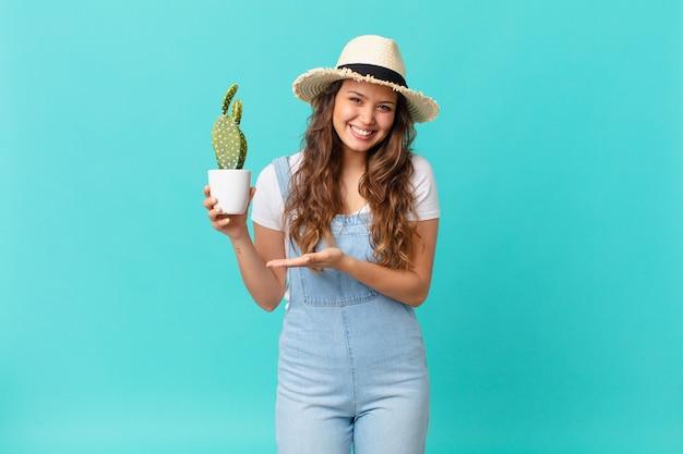 Jonge mooie vrouw die vrolijk lacht, zich gelukkig voelt en een concept toont en een cactus vasthoudt