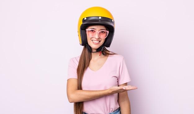 Jonge mooie vrouw die vrolijk lacht, zich gelukkig voelt en een concept toont. motorrijder en helm