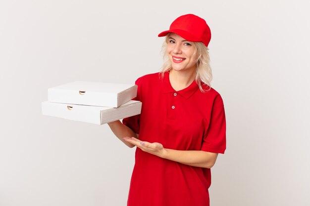 Jonge mooie vrouw die vrolijk lacht, zich gelukkig voelt en een concept toont. pizza bezorgconcept