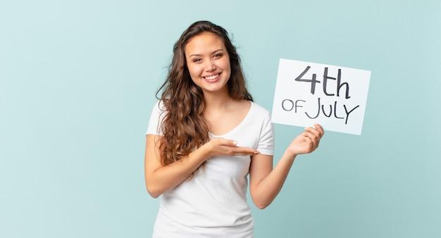 Jonge mooie vrouw die vrolijk lacht, zich gelukkig voelt en een concept van de onafhankelijkheidsdag toont