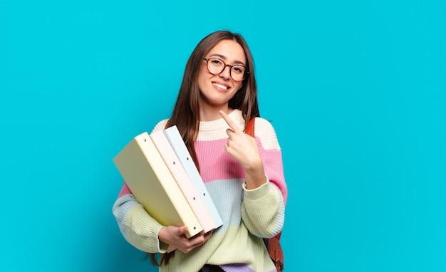 Jonge mooie vrouw die vrolijk lacht, zich gelukkig voelt en naar de zijkant en naar boven wijst, een object in de kopieerruimte laat zien