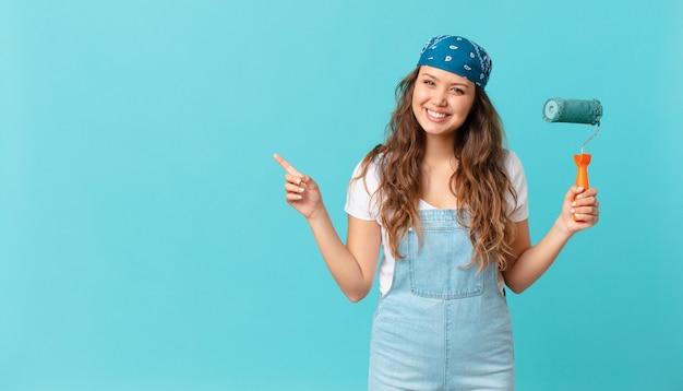 Jonge mooie vrouw die vrolijk lacht, zich gelukkig voelt en naar de zijkant wijst en een muur schildert