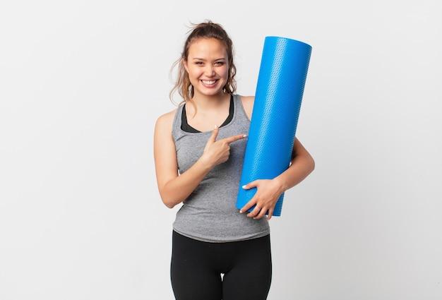 Jonge mooie vrouw die vrolijk lacht, zich gelukkig voelt en naar de zijkant wijst en een yogamat vasthoudt