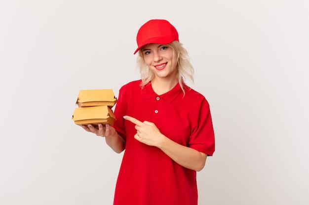 Jonge mooie vrouw die vrolijk lacht, zich gelukkig voelt en naar de zijkant wijst. hamburger bezorgconcept
