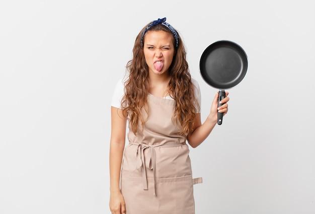 Jonge mooie vrouw die walgt en geïrriteerd voelt en een chef-kokconcept uitspreekt en een pan vasthoudt