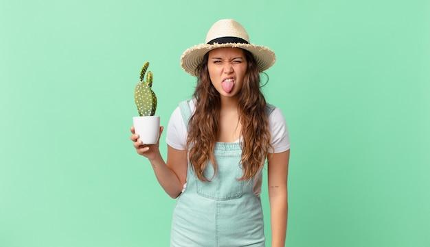 Jonge mooie vrouw die walgt en geïrriteerd voelt en haar tong uitsteekt en een cactus vasthoudt