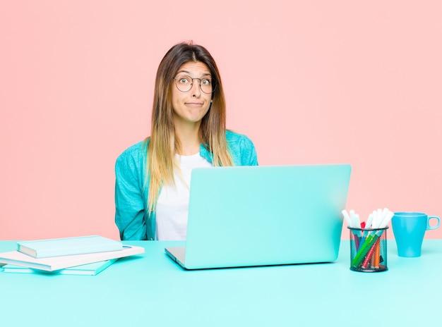 Jonge mooie vrouw die werkt met een laptop die zich verdrietig en gestrest voelt, overstuur vanwege een slechte verrassing, met een negatieve, angstige blik