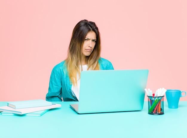 Jonge mooie vrouw die werkt met een laptop die zich verdrietig, overstuur of boos voelt en naar de kant kijkt met een negatieve houding, fronsen in onenigheid
