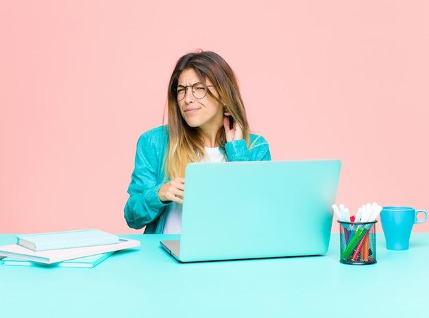 Jonge mooie vrouw die werkt met een laptop gevoel gestrest, gefrustreerd en moe, wrijven pijnlijke nek, met een bezorgd, onrustige blik