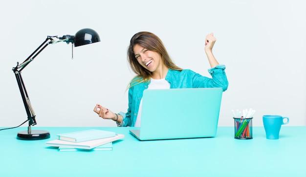 Jonge mooie vrouw die werkt met een laptop glimlachen, zorgeloos, ontspannen en gelukkig voelen, dansen en luisteren naar muziek, plezier maken op een feestje