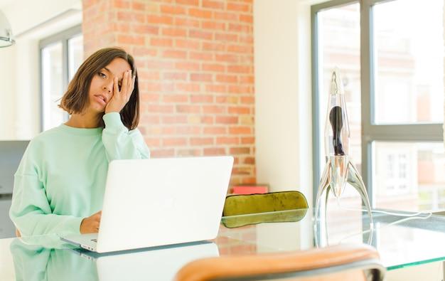 Jonge mooie vrouw die werkt, zich verveeld, gefrustreerd en slaperig voelt na een vermoeiende, saaie en vervelende taak, gezicht met de hand vasthoudt