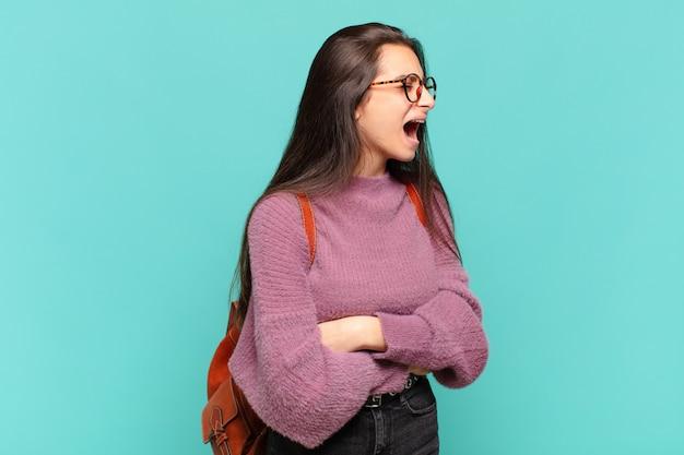 Jonge mooie vrouw die woedend schreeuwt, agressief schreeuwt, gestrest en boos kijkt