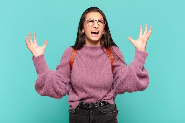 Jonge mooie vrouw die woedend schreeuwt, zich gestrest en geïrriteerd voelt met de handen in de lucht en zegt waarom ik. studentenconcept