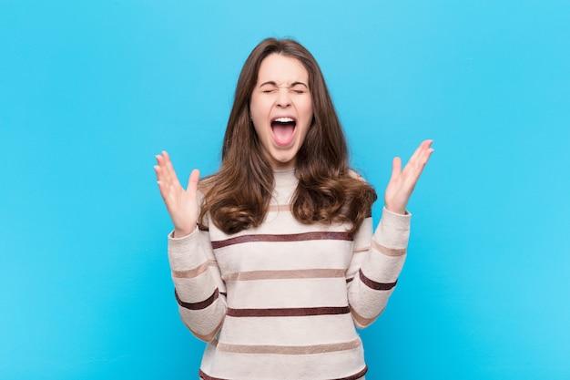 Jonge mooie vrouw die woedend schreeuwt, zich gestrest en geïrriteerd voelt met handen omhoog in de lucht en zegt waarom ik tegen de blauwe muur