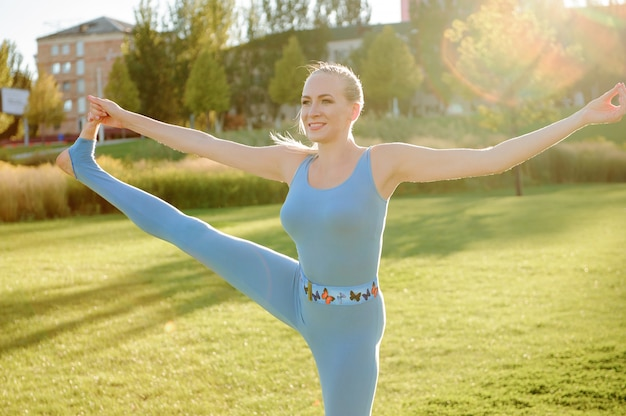 Jonge mooie vrouw die yogaoefeningen in park doet