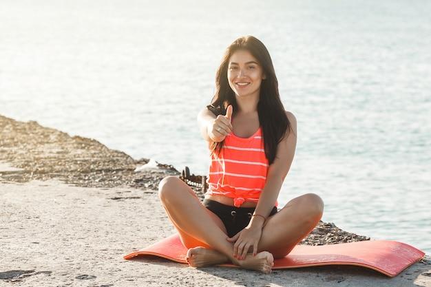 Jonge mooie vrouw die yogaoefeningen op het strand doet