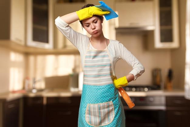 Jonge mooie vrouw die zich bezighouden met het schoonmaken van de keuken