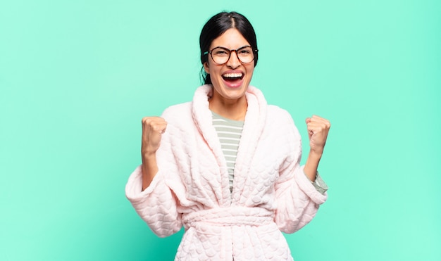 Jonge mooie vrouw die zich blij, verrast en trots voelt, schreeuwt en succes viert met een grote glimlach