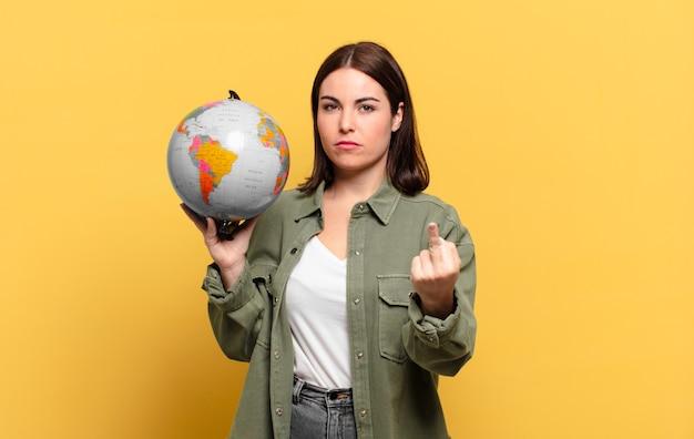 Jonge mooie vrouw die zich boos, geïrriteerd, rebels en agressief voelt, de middelvinger omdraait, terugvecht