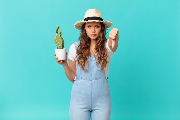 Jonge mooie vrouw die zich boos voelt, duimen naar beneden laat zien en een cactus vasthoudt