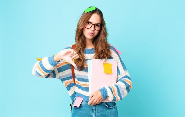 Jonge mooie vrouw die zich boos voelt, duimen naar beneden laat zien met een tas en boeken vasthoudt