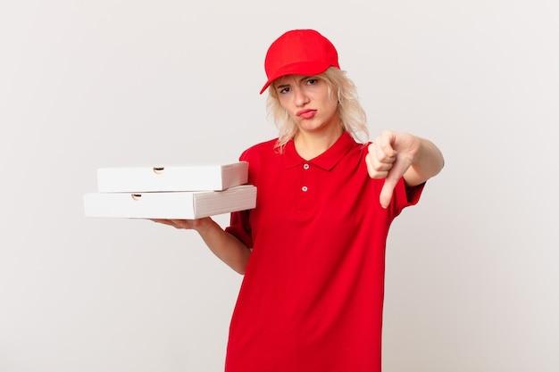 Jonge mooie vrouw die zich boos voelt en duimen naar beneden laat zien. pizza bezorgconcept