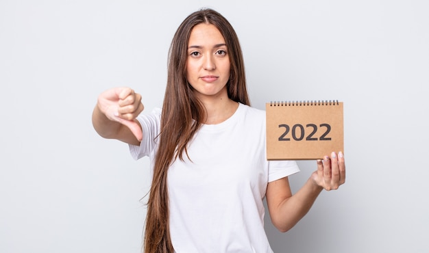 Jonge mooie vrouw die zich boos voelt en duimen naar beneden laat zien. plannerconcept 2022