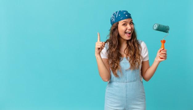 Jonge mooie vrouw die zich een gelukkig en opgewonden genie voelt na het realiseren van een idee en het schilderen van een muur