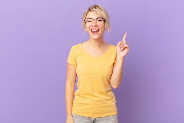Jonge mooie vrouw die zich een gelukkig en opgewonden genie voelt na het realiseren van een idee