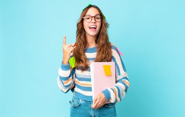 Jonge mooie vrouw die zich een gelukkig en opgewonden genie voelt nadat ze een idee heeft gerealiseerd met een tas en boeken vasthoudt