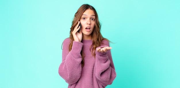 Jonge mooie vrouw die zich extreem geschokt en verrast voelt en een smartphone gebruikt
