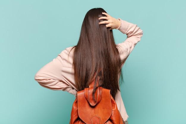 Jonge mooie vrouw die zich geen idee en verward voelt, een oplossing denkt, met de hand op de heup en andere op het hoofd