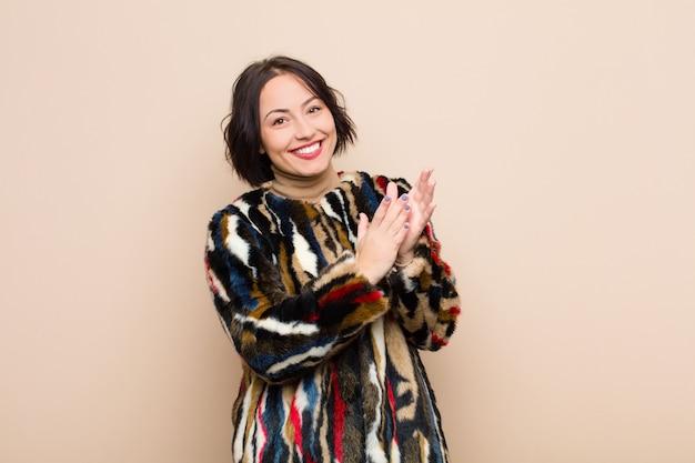 Jonge mooie vrouw die zich gelukkig en succesvol voelt, glimlachend en klappende handen, gefeliciteerd met een applaus tegen beige muur
