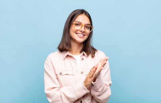 Jonge mooie vrouw die zich gelukkig en succesvol voelt, lacht en klapt in de handen, gefeliciteerd met een applaus