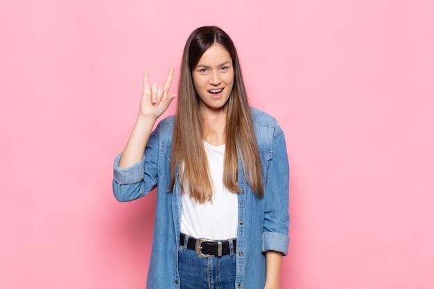 Jonge mooie vrouw die zich gelukkig, leuk, zelfverzekerd, positief en rebels voelt en rock of heavy metal met de hand tekent
