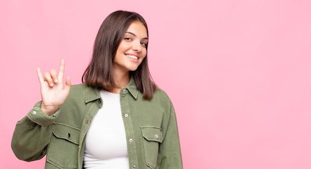 Jonge mooie vrouw die zich gelukkig, leuk, zelfverzekerd, positief en rebels voelt